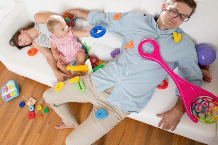 Zmęczeni rodzice leżą z dzieckiem na kanapie