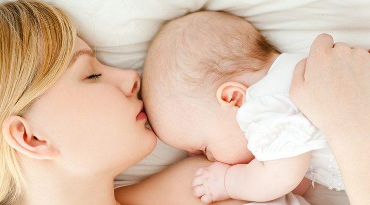 Młoda mama leży z niemowlakiem