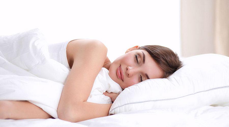 Zrelaksowana kobieta śpiąca w łóżku